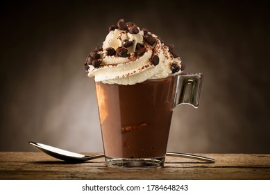 Cup of coffee with whipped cream, cocoa powder and chocolate chips.