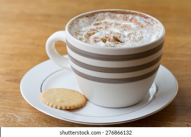 A cup of coffee with whipped cream in an oversize mug