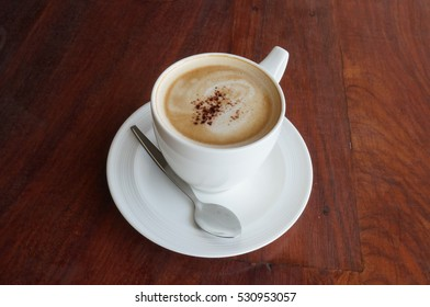 A cup of coffee in a white ceramic cup with teaspoon on wooden background, close up
