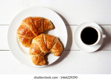 Cup of coffee and white dish with croissants on white wooden background.