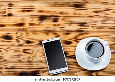 A cup of coffee and a white smartphone on a wooden office desk or on a table in a cafe