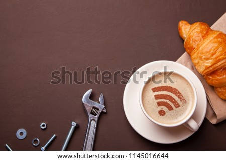 Cup of coffee with WiFi sign on the foam. Free access point to the Internet WiFi. I like coffee break with croissant. Repair service concept. Technical support, wrench