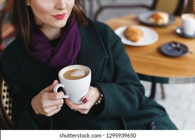 Cup of coffee in women's hands. Beautiful young brunette woman wearing green coat sitting at a table in cozy street outdoor cafe and drinking coffee. Girl with cup of cappuccino at restaurant terrace.