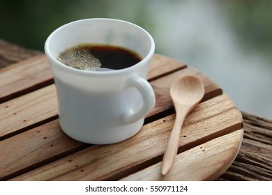 A cup of coffee with wooden spoon on the wooden plate and old table.