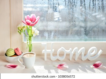 """Cup of coffee, word """"Home"""", pink tulips and white freesia on the window board on a rainy day in Spring"""