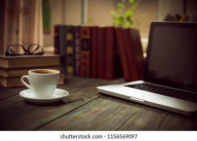 A cup of coffee in the workplace on a wooden table. A cup of coffee in the workplace on a wooden table. The concept of working outside the office