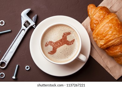 Cup of coffee with  wrench on the foam. I like a coffee break with  croissant. Repair service concept. Technical support. Different tools