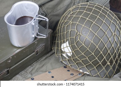 a cup of coffee with ww2 period us army military equipment on green uniform background concept