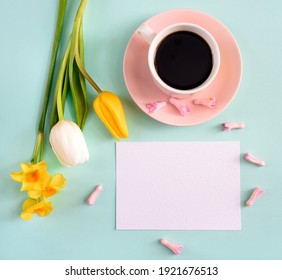 A cup of coffee and yellow tulips with empty blank on a blue background. Concept of holiday, birthday, easter, womens day. Flat lay, top view, space for text