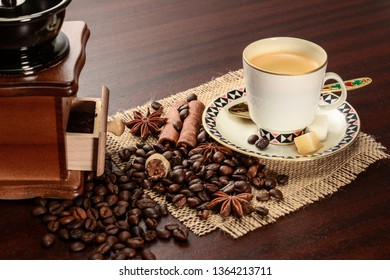 Cup of coffeee with saucer on a jute napkin. Vintage still life on wooden table, with sugar, anise, cinnamon, grinder and dropped coffee beans
