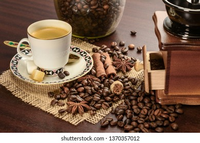 Cup of coffeee with saucer on a jute napkin. Vintage still life on wooden table, with sugar, anise, cinnamon, grinder and coffee jar