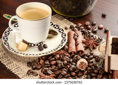 Cup of coffeee with saucer on a jute napkin. Vintage still life on wooden table, with sugar, anise, cinnamon, grinder and coffee jar, close-up