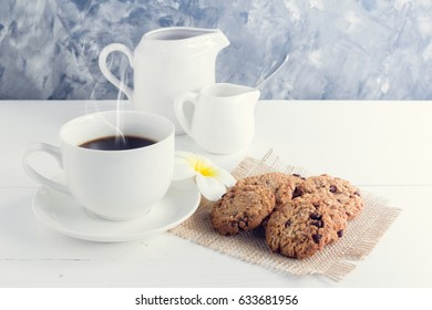cup of coffee,milk,sugar,chocolate chip cookies  on white wooden background with loft wall style with light in concept relax time