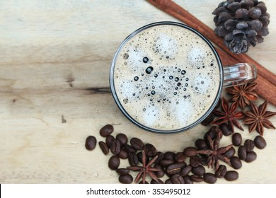 cup of coffie with cinnamon and star anise on wooden background