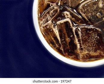 Cup of cola against blue textured background