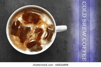 Cup of cold brewed coffee with milk on gray background