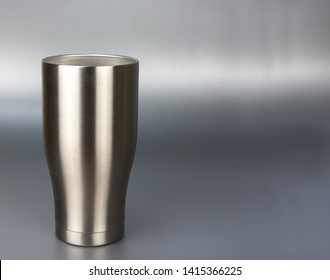 Cup cold storage. Tumbler glass cold store. Stainless steel thermos tumbler mug on gray background.