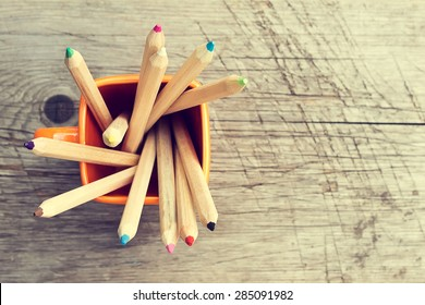 Cup with colorful Pencils on wooden table. Top view. Toned image