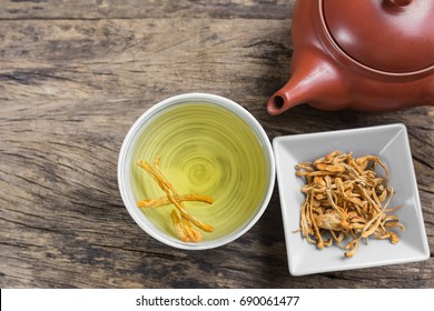 cup of cordyceps (chong cao) tea on old and crack wooden surface with copy space, healthy beverage concept.
