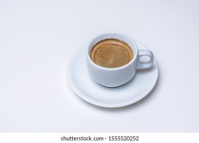 Cup of creamy coffee on the top of a slightly textured white desk