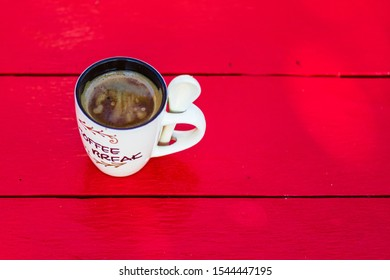 Cup of creamy homemade expresso coffee on red wooden board.