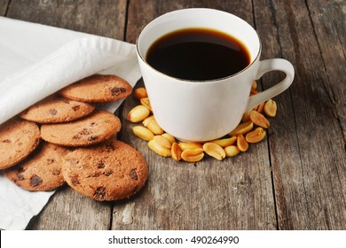 cup of dark coffee, with chocolate cookies and peanuts