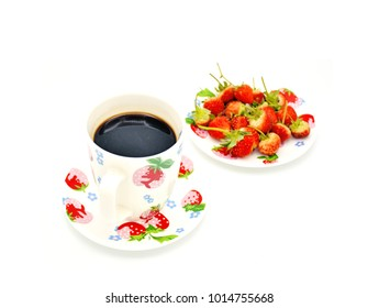a cup of dark coffee and unfocus fresh organic strawberry from the garden. Nice combination in the morning. Freshness.  Red rips strawberry in unfocus background. Isolated on white back ground.