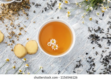 Cup of delicious camomile tea and ginger on wooden table