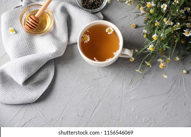 Cup of delicious camomile tea and honey on light table