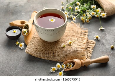 Cup of delicious camomile tea on table