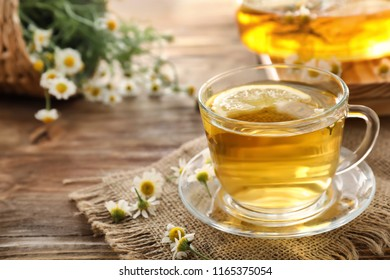 Cup of delicious camomile tea on wooden table