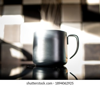 Cup of delicious coffee prepared at sunrise in the kitchen