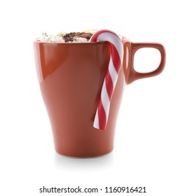 Cup of delicious hot chocolate and candy cane on white background
