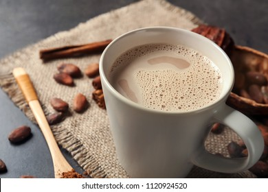 Cup of delicious hot cocoa on grey background, closeup