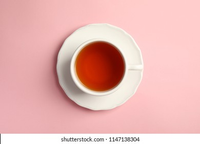 Cup of delicious tea with saucer on color background, top view