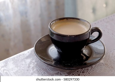 A cup of designed coffee on table beside window with vintage flower curtain and sun light in the afternoon, relax environment in warm day for friends, family or lovers at home or restaurant