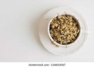 Cup with dried chamomile tea on white table. Herbal drink, top view