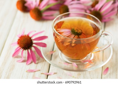 Cup of echinacea tea on white wooden table