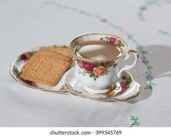 Cup of English tea on a table cloth with biscuits