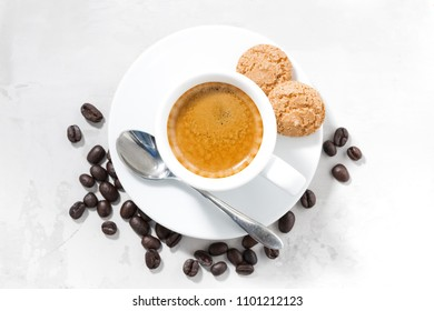 cup of espresso and almond cookies on a white table, top view, horizontal