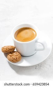 cup of espresso and almond cookies on a white table, vertical, closeup