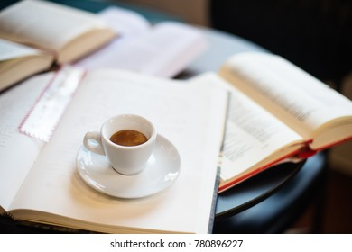 Cup of espresso among a lot of opened books