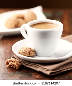 Cup of espresso with biscotti. Rustic wooden background. Close up.