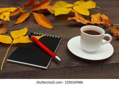 Cup of espresso, black notebook and pen among autumn leaves on a wooden background