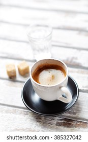 Cup of Espresso and brown sugar cubes on wooden background.