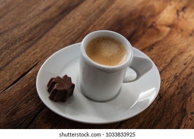 A cup of espresso with a chocolate candy maple leaf shaped on wooden background