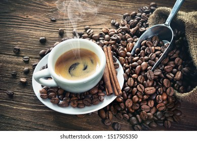 Cup of espresso with coffee beans, bag, scoop and steam on rustic wooden background