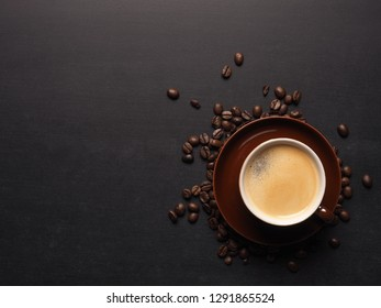 Cup of an espresso with coffee beans on a chalkboard, space for text or your image on the left side