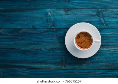 A cup of espresso coffee on a dark wooden background. Top view. Free space for text.