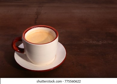 A cup of espresso coffee on a dark wooden background